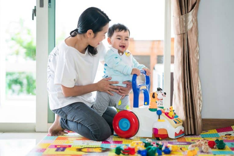 Asian mother and baby training walking with walker toy