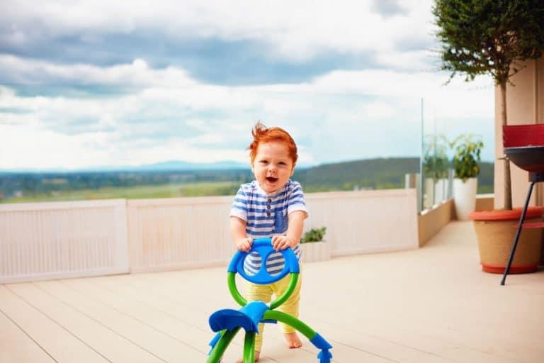 a toddler baby boy pushing pushing go cart, outdoors