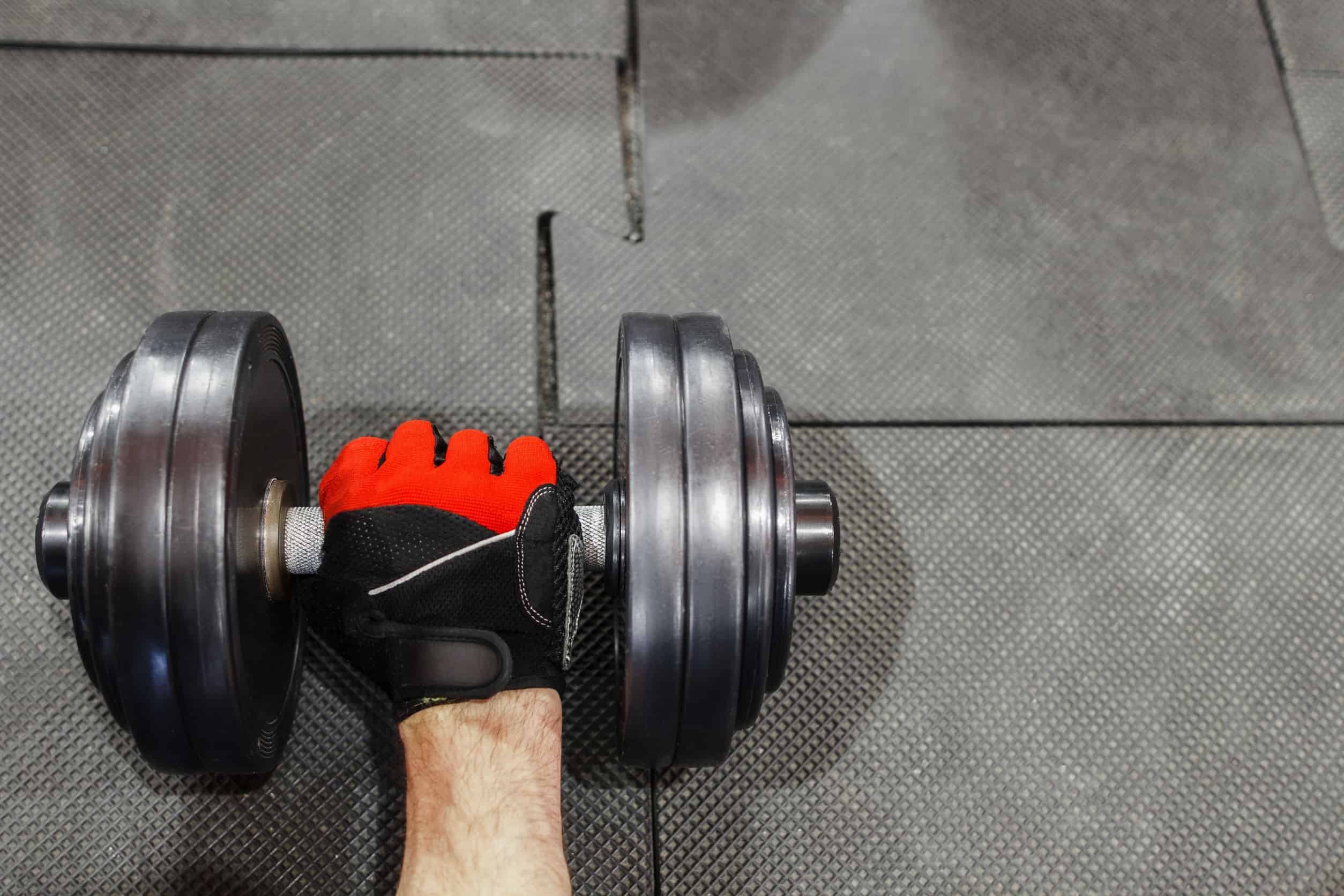 Male hand in sport glove holding dumbbell void