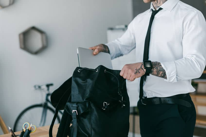 bijgesneden schot van jonge getatoeëerde zakenman laptop in de rugzak