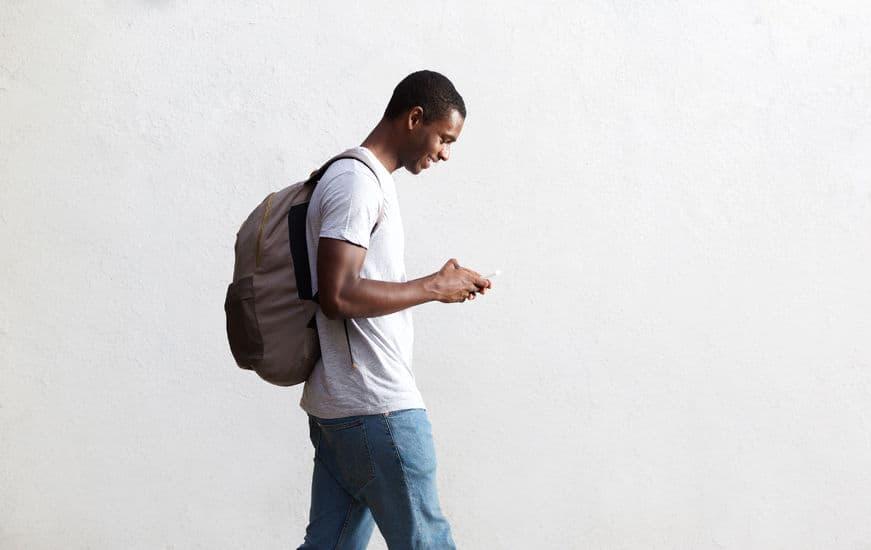 zijaanzicht portret van een Afro-Amerikaanse student wandelen met tas en mobiele telefoon