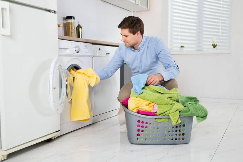Man laden van kleren in de wasmachine