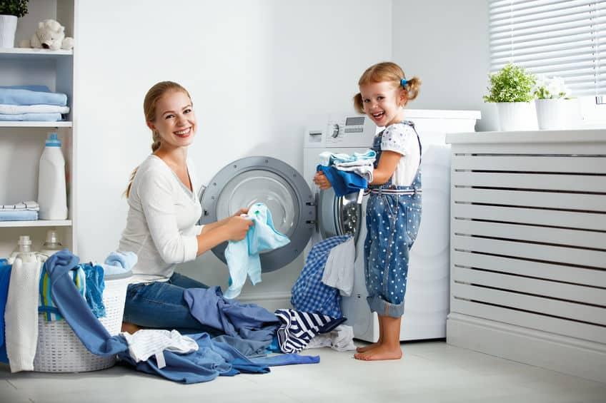 familie moeder en kind meisje in wasruimte in de buurt van wasmachine