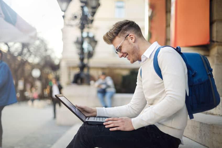 man kijken naar zijn laptop op straat
