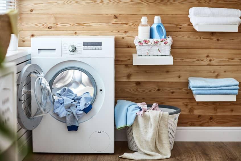 Binnenland van echte wasruimte met wasmachine bij venster thuis