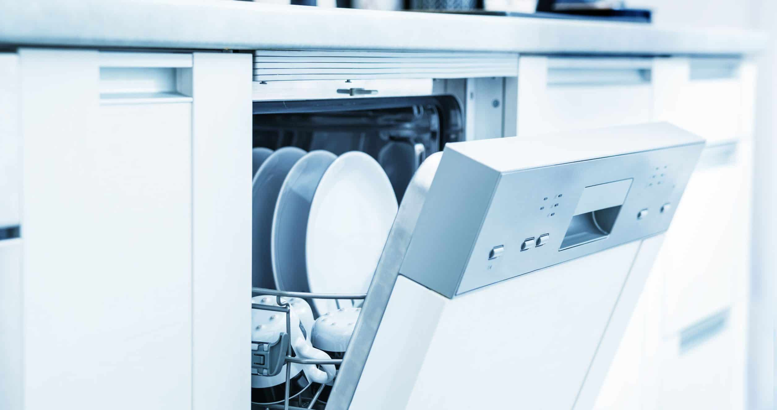 Open vaatwasser met schone gerechten in witte keuken
