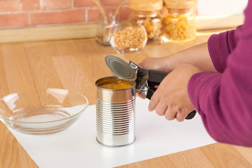 vrouw het openen van een blikje maïs met blikopener