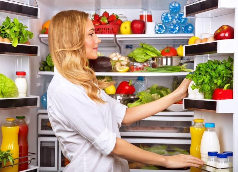Het gelukkige wijfje zoekt iets in de koelkast