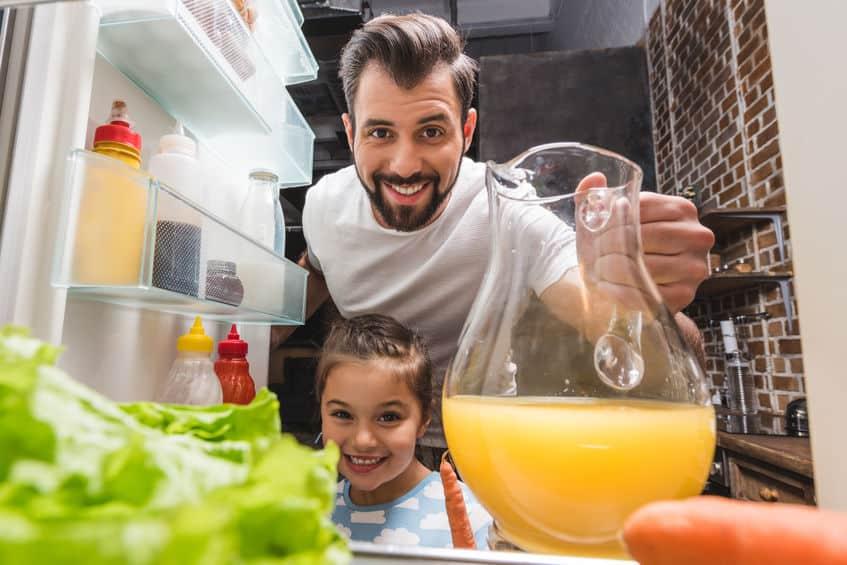vader en dochter nemen sap uit koelkast