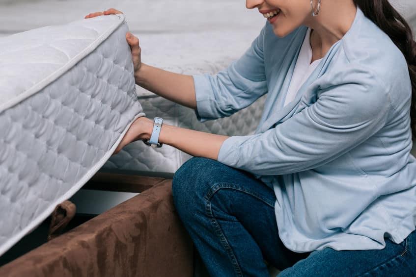 bijgesneden schot van lachende vrouw kiezen orthopedische matras in meubelwinkel