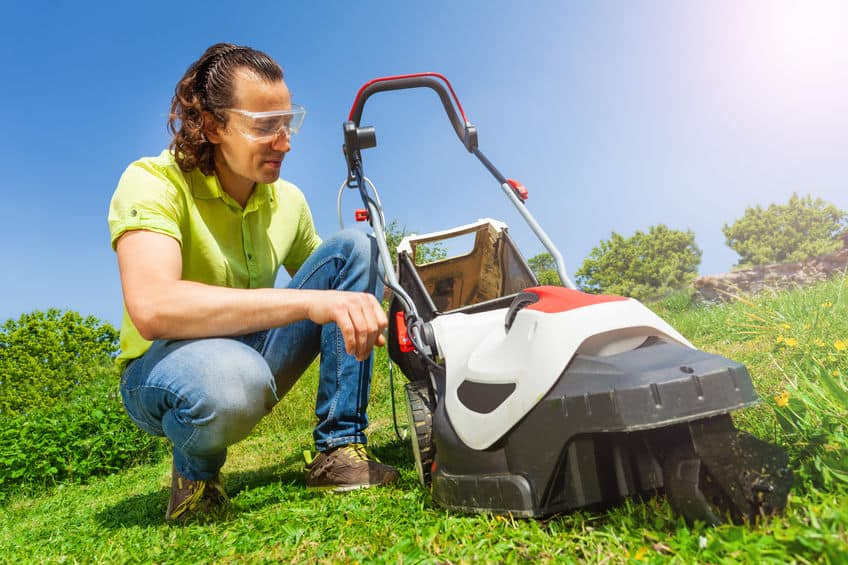 Tuinman gras vak van de grasmaaier schoonmaken