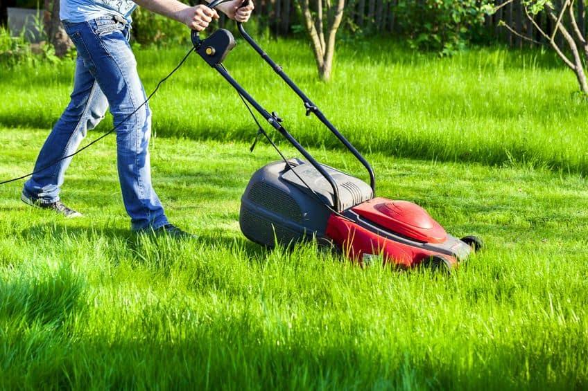man beweegt met grasmaaier maait groen gras
