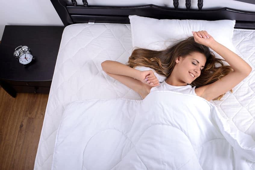 jonge mooie vrouw die 's ochtends volledig uitgerust wakker wordt.
