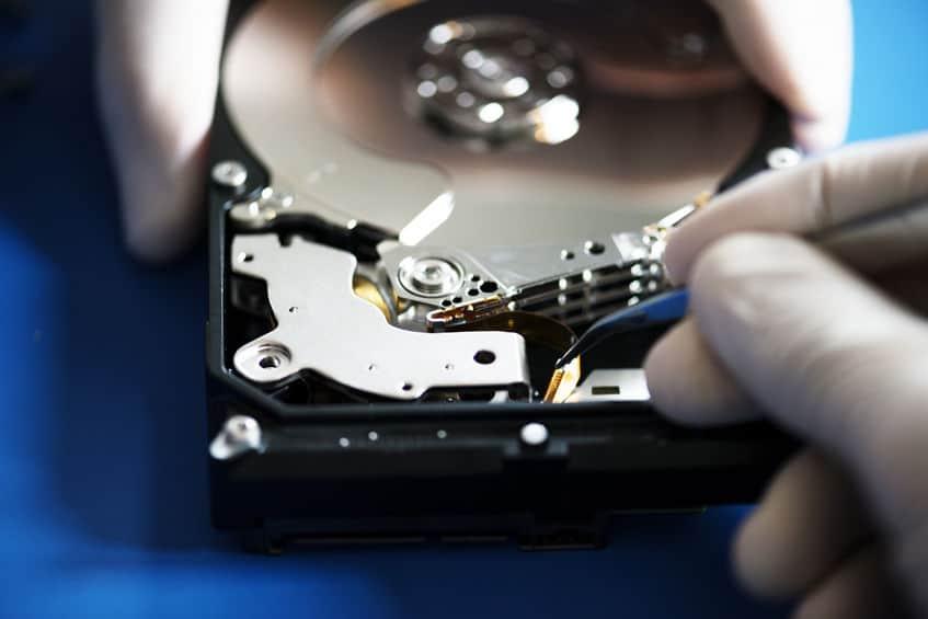 Close-up van handen met pincet en computerharde schijf