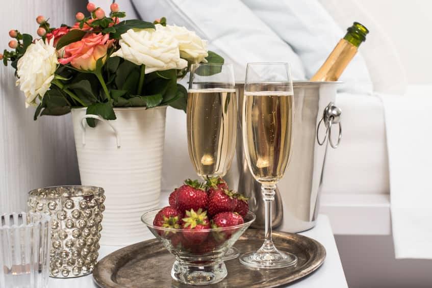 Champagne in bed met aardbeien