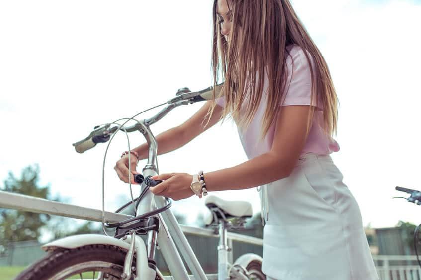 Een meisje staat met een fiets in de zomer in de stad.