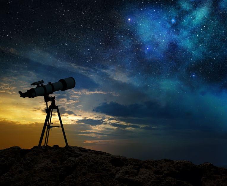 melkweg bij dageraad en silhouet van een telescoop