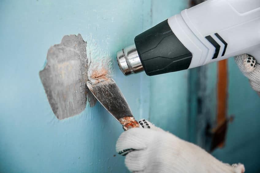Master verwijdert oude blauwe verf van betonnen muur met warmtepistool en schraper. Detailopname