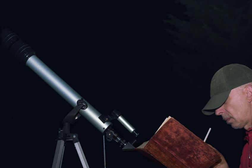 Man Met Boek Dichtbij Telescoop