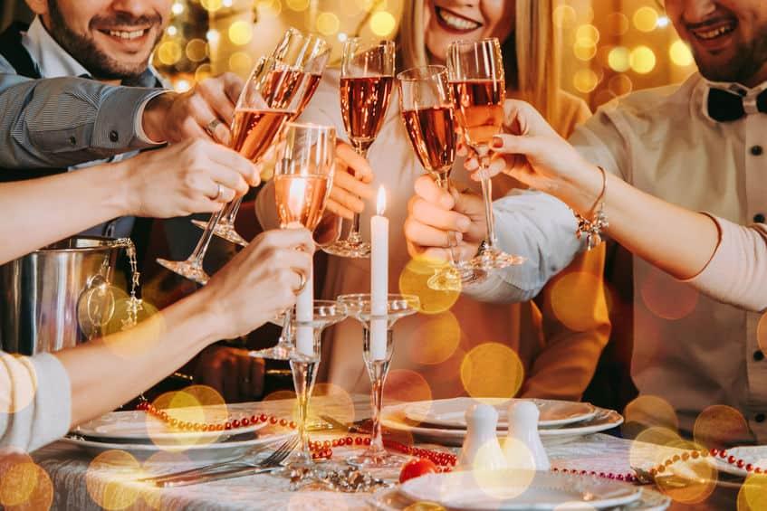 Vrienden vieren kerst- of oudejaarsavond. Feesttafel met roze champagne.