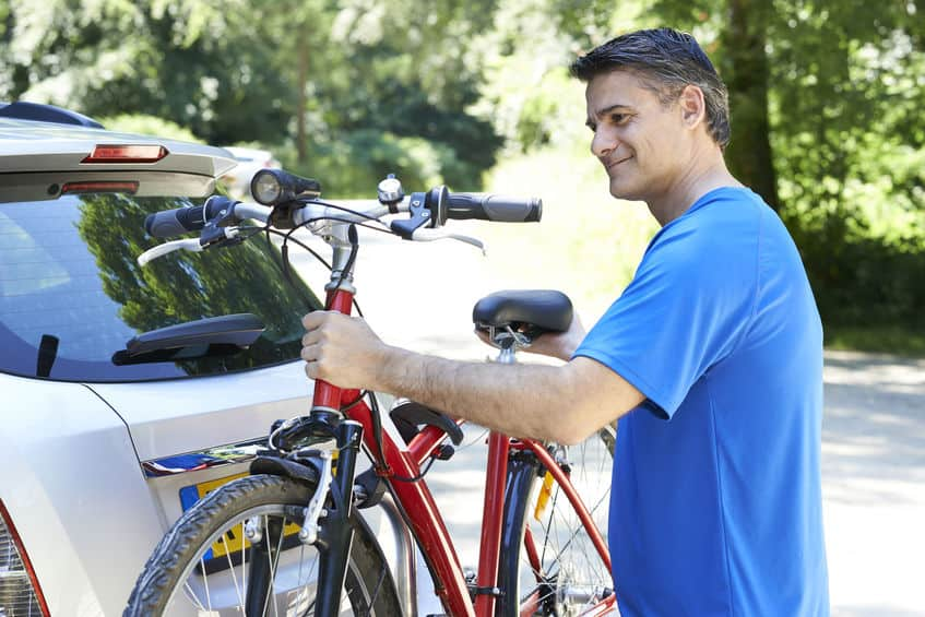 oudere man met zijn mountainbike met de auto