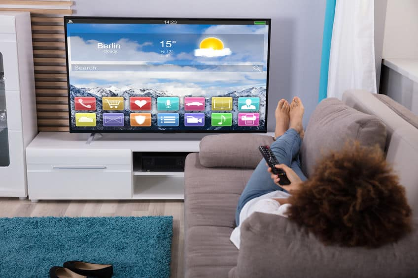 familie samen televisie kijken moderne tv op een minimalistische woonkamer Vrouwenzitting Op Bank Die Afstandsbediening Met Behulp Van Moderne woonkamer met stereo speakers Vrouw televisiekijken met kleurrijke toepassingen op het scherm
