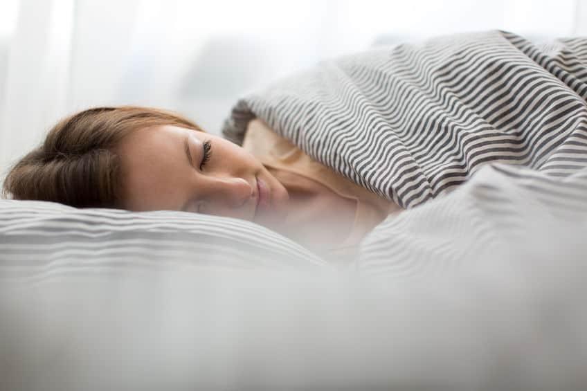 mooie jonge vrouw slapen in bed