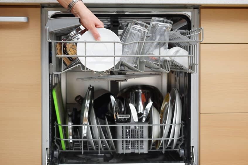 vrouw gebruikt een vaatwasser in een moderne keuken