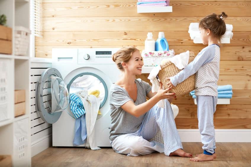 Gelukkige familie moeder huisvrouw en kind in wasgoed met wasmachine