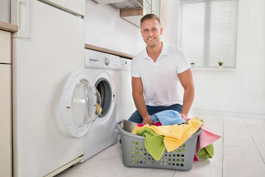 Man Kleurrijke Handdoeken In De Wasmachine Zetten