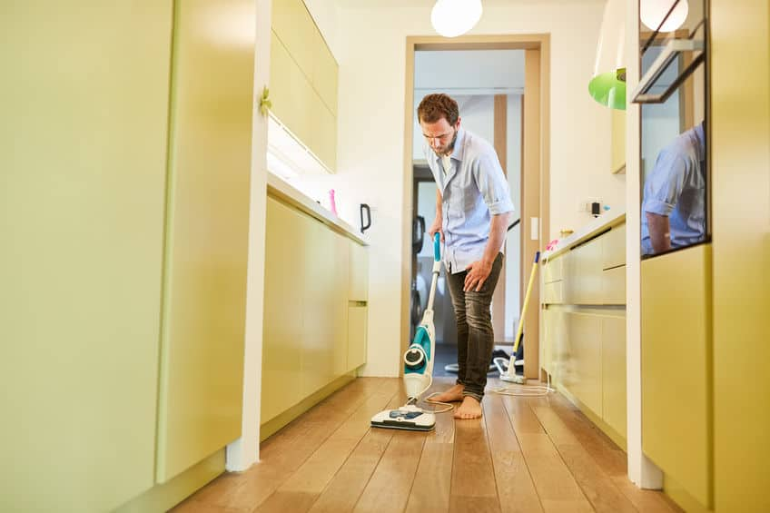 Huishoudster reinigt parketvloer in gang