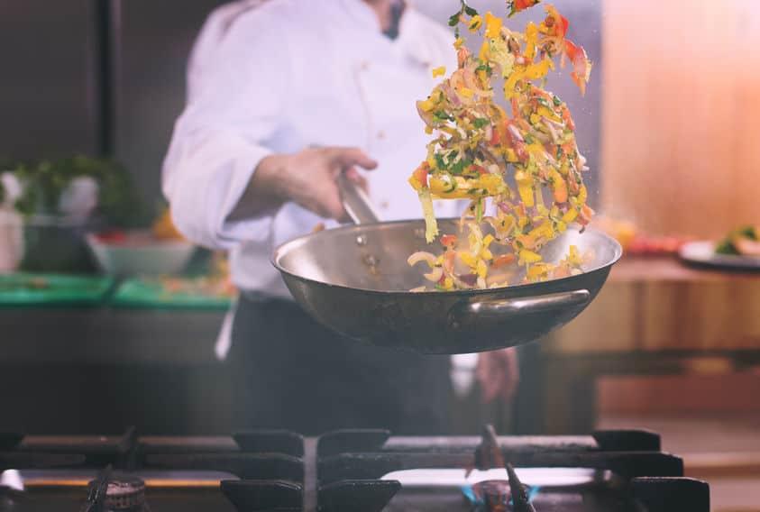 chef-kok die groenten in wok wegknipt