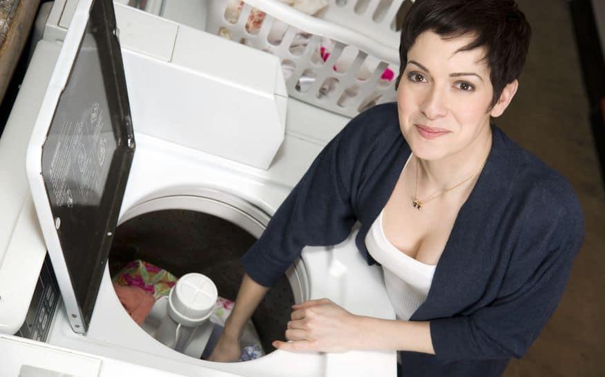 een vrouw haalt kleren uit de wasmachine bij de wasserette