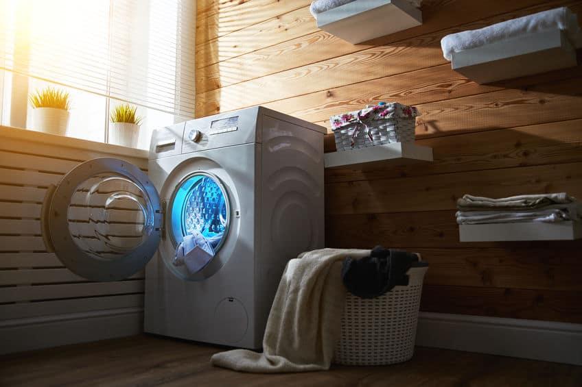 Interieur van echte wasruimte met wasmachine bij raam thuis