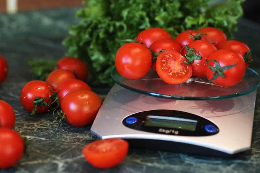 Verse tomaten op keukenweegschaal het wegen