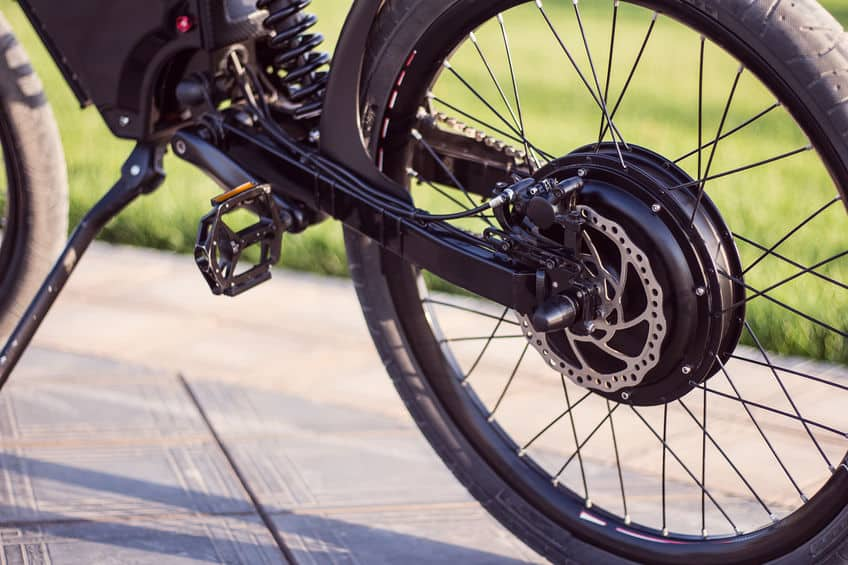 Elektrisch fietsmotorwiel van dichtbij met pedaal en achterschokdemper