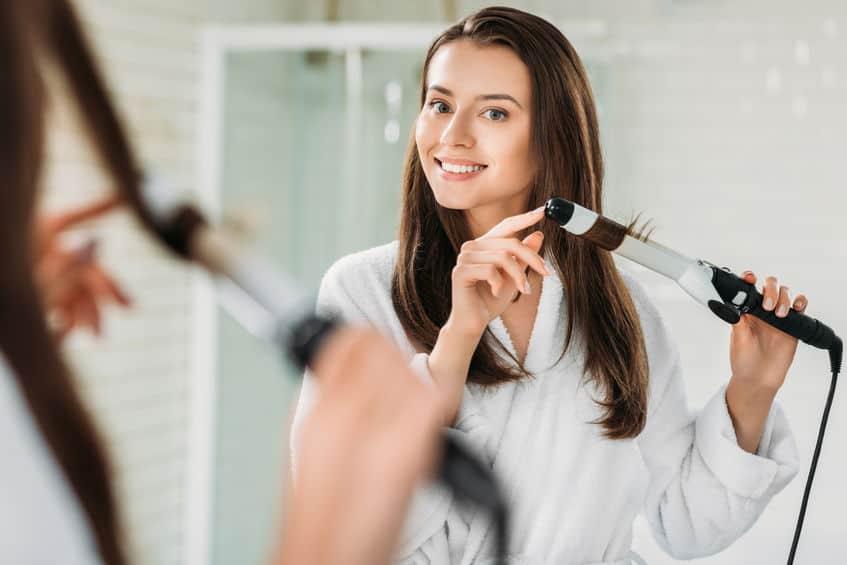 gelukkig brunette meisje in badjas met behulp van haarkruller bij de spiegel in de badkamer