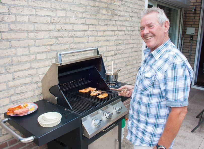 gepensioneerde nederlandse senior man hamburgers grillen in zijn achtertuin op een zomerse dag