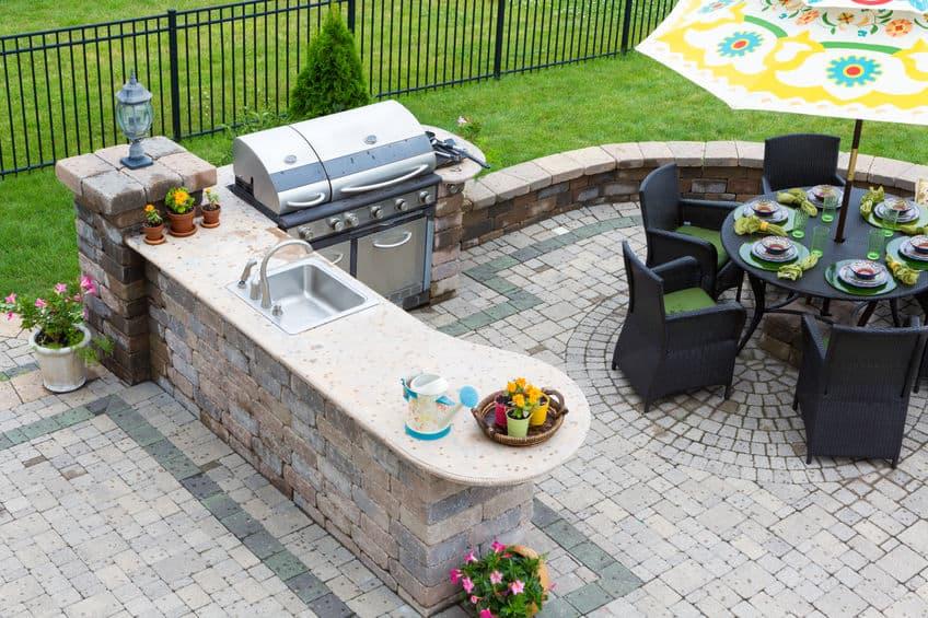 Buitenkeuken en eettafel op een betegeld terras