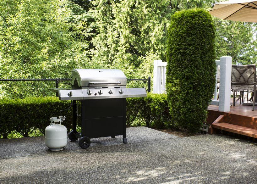 horizontale foto van een groot barbecue fornuis op betonnen terras met bos en dek op de achtergrond