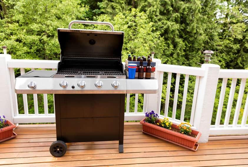 Open barbecue-fornuis en flessen bier op cederhouten buitenterras