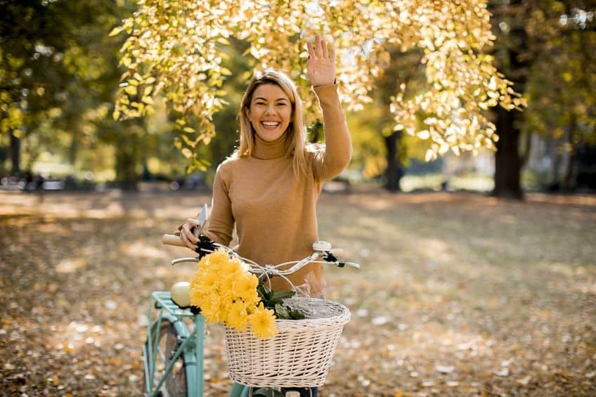Gelukkig actieve vrouw fietsten in herfst park