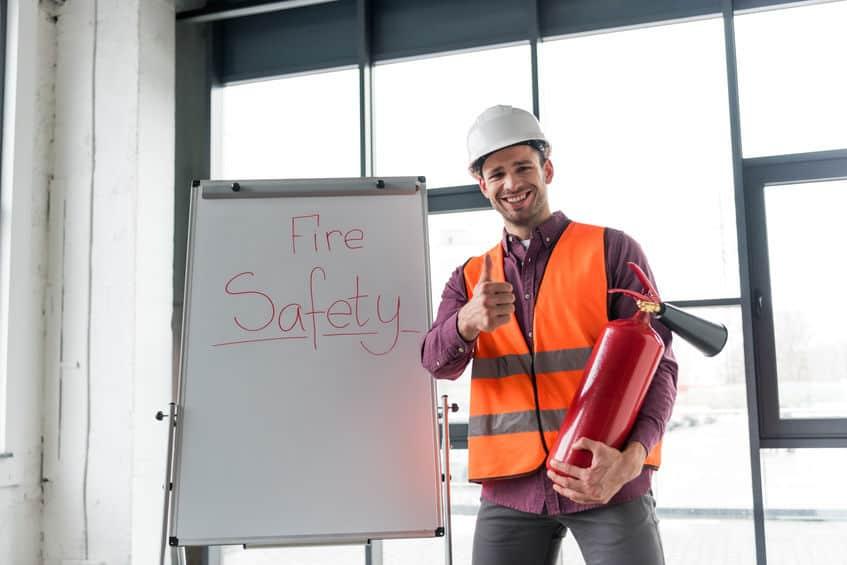 vrolijke brandweerman die rode brandblusser houdt en duim toont terwijl hij in de buurt van een wit bord staat met brandveiligheidsopschriften