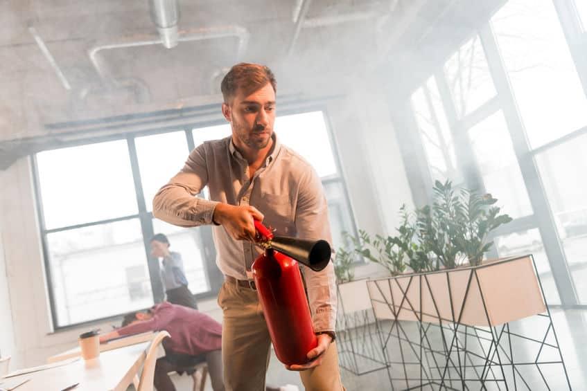 knappe zakenman brandblusser bedrijf in kantoor met rook in de buurt van collega's