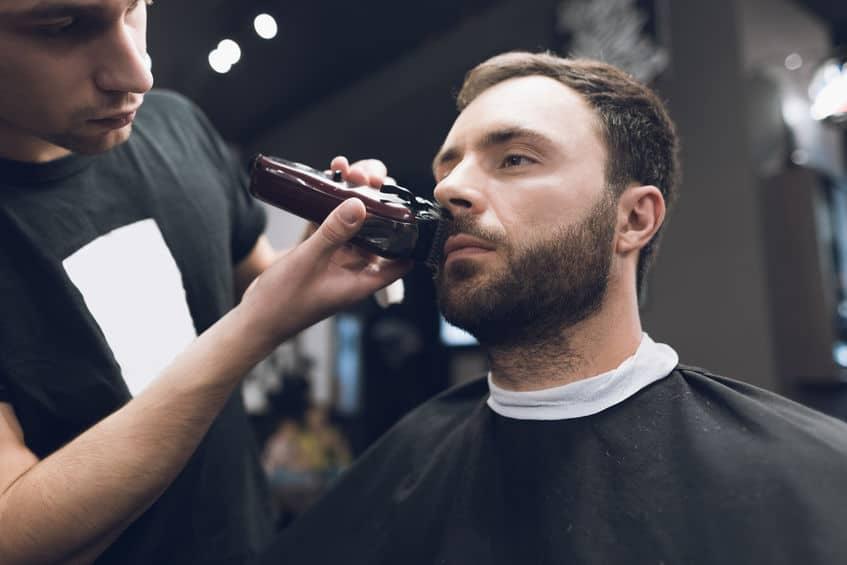 Kapper snijdt een baard aan een man in een kapsalon.