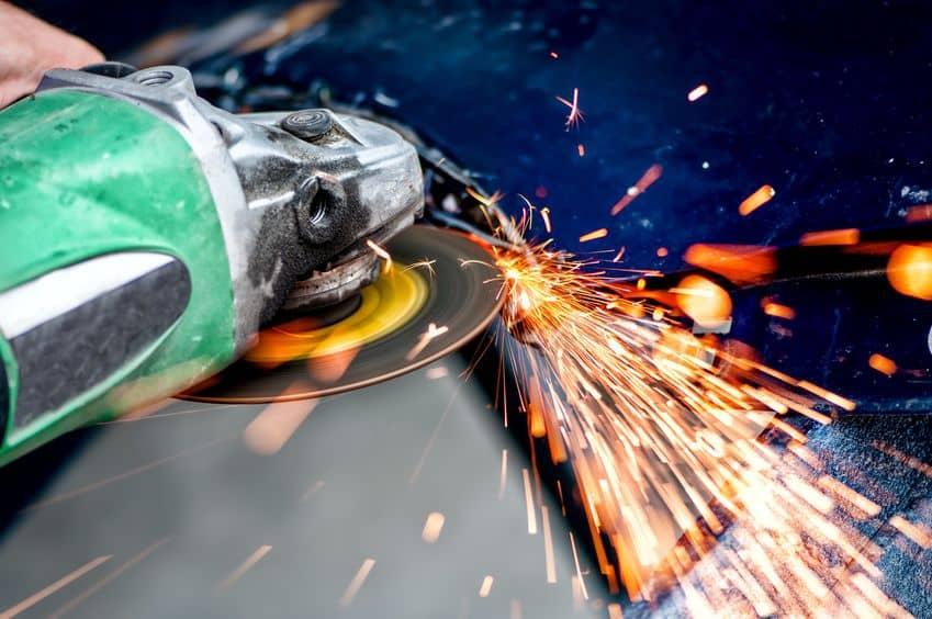 snijden van een tegel met behulp van een haakse slijper zware industrie werknemer snijden staal met haakse slijper in werkplaats, bij autoservice