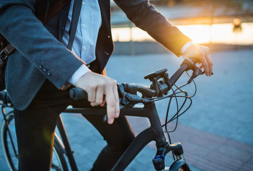 Middendeel van zakenman forensen met elektrische fiets reizen van het werk in de stad.