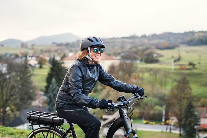Een zijaanzicht van seniorenvrouw met elektrofietsen in de buitenlucht op het platteland.