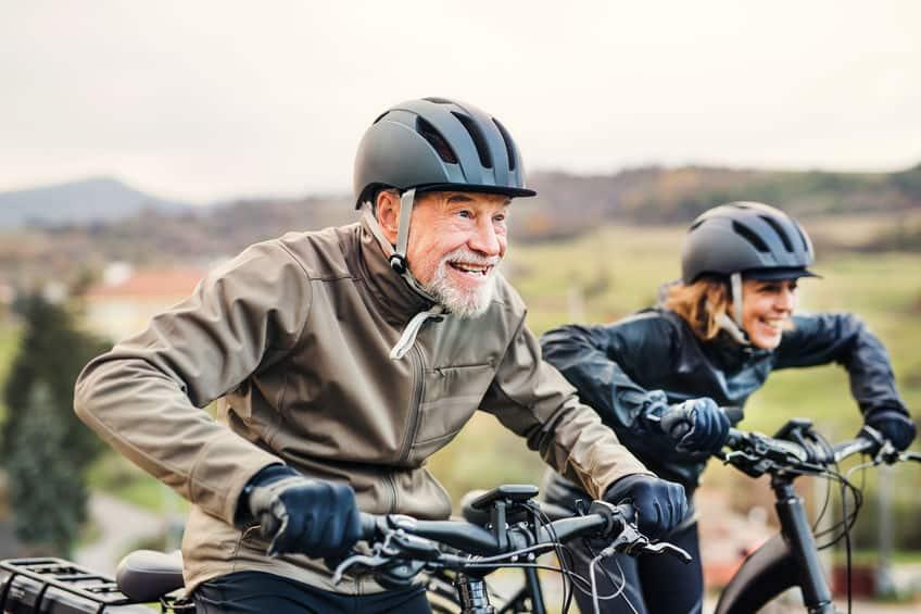 Actief seniorenpaar met elektrofietsen die buiten fietsen op een weg in de natuur.