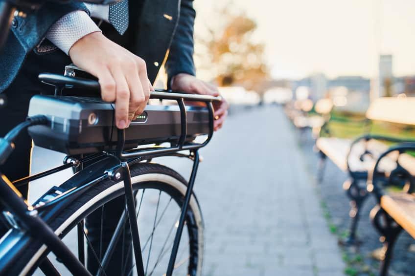 Een middendeel van een zakenman forens die een elektrische fiets in de stad opzet.